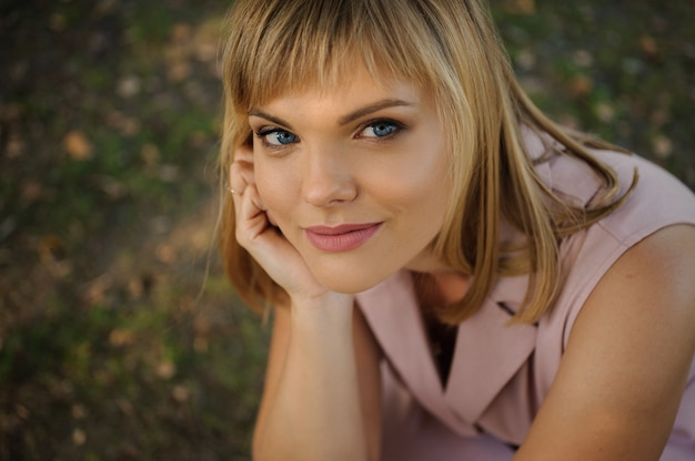 Portret piękny kobiety obsiadanie na zielonej trawie w parku