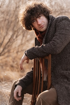 Portret piękny kręcone młody człowiek w przyrodzie na krześle