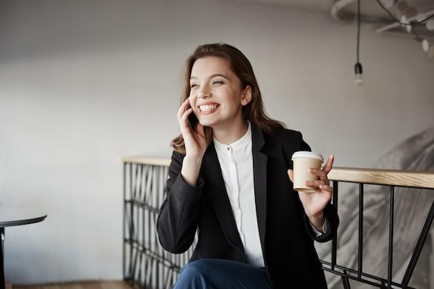 Portret piękny mądrze europejski kobiety obsiadanie w kawiarni pije kawę i gestykuluje, podczas gdy opowiadający na smartphone