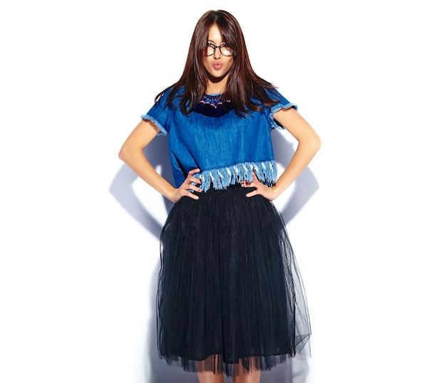 Portret piękny mądrze uśmiechnięty modniś brunetki kobiety model w przypadkowych eleganckich niebieskich dżinsach odziewa i szkła odizolowywający na bielu daje buziakowi
