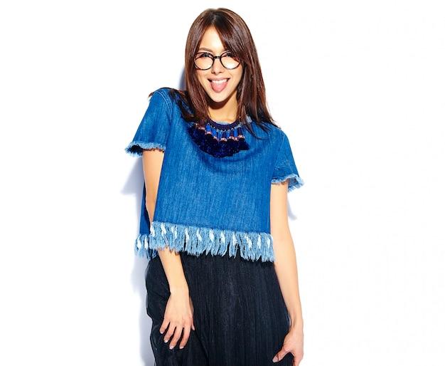 Portret piękny mądrze uśmiechnięty modniś brunetki kobiety model w przypadkowych eleganckich niebieskich dżinsach odziewa i szkła odizolowywający na bielu pokazuje jej jęzor