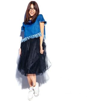 Portret piękny mądrze uśmiechnięty modniś brunetki kobiety model w przypadkowych eleganckich niebieskich dżinsach odzieżowych i szkłach odizolowywających na bielu. pełna długość