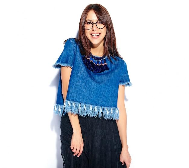Portret piękny mądrze uśmiechnięty modniś brunetki kobiety model w przypadkowych eleganckich niebieskich dżinsach odzieżowych i szkłach odizolowywających na bielu