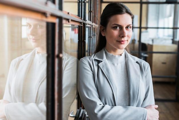 Portret piękny młody bizneswoman z ręką krzyżującą