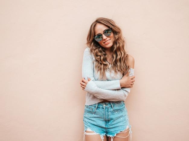 Portret piękny model uśmiechający się ubrany w letnie spodenki jeansy hipster. przytulanie się