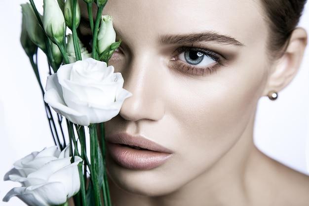 Portret piękny model z dobrą skórą na białym tle z kwiatem białych róż.