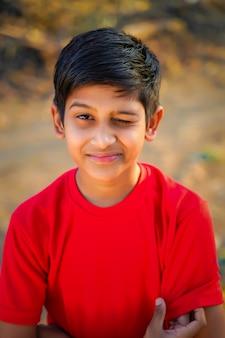 Portret piękny mrugający chłopiec w czerwonej koszulce