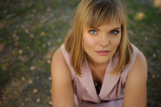 Portret piękny poważny kobiety obsiadanie na zielonej trawie w parku