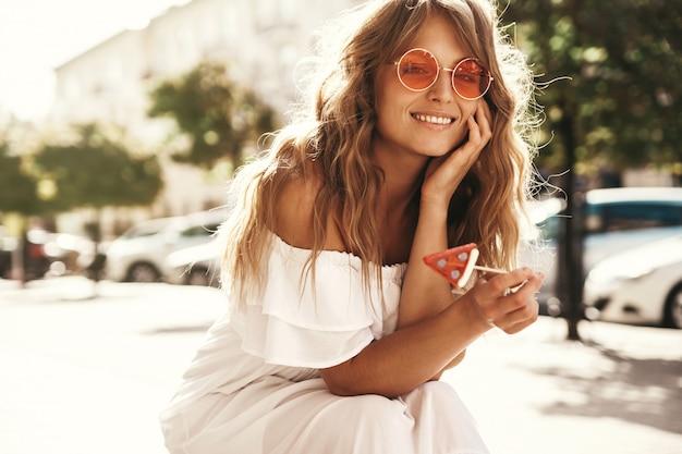 Portret piękny śliczny blond nastolatka model bez makeup w lato modnisia bielu sukni odziewa z arbuza cukierku obsiadaniem na ulicznym tle