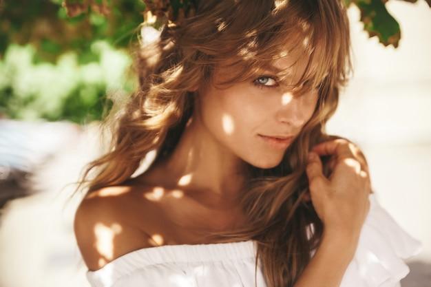 Portret piękny śliczny blond nastolatka model bez makeup w lato modnisia bielu sukni ubraniach pozuje na ulicznym tle. promienie słoneczne na twarzy