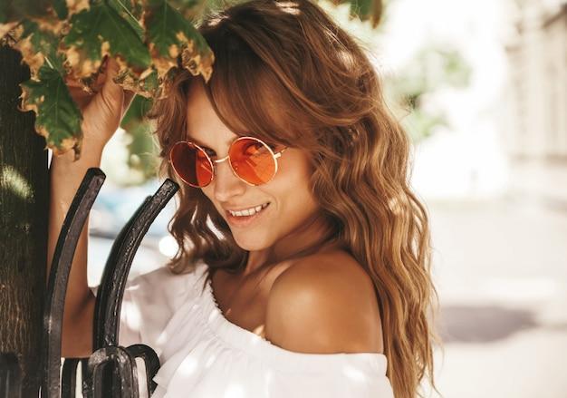 Portret piękny śliczny blond nastolatka model bez makeup w lato modnisia bielu sukni ubraniach pozuje na ulicznym tle w okularach przeciwsłonecznych blisko drzewnych liści