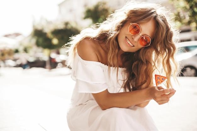 Portret piękny śliczny blond nastolatka model bez makeup w lato modnisia bielu sukni ubraniach siedzi na ulicznym tle
