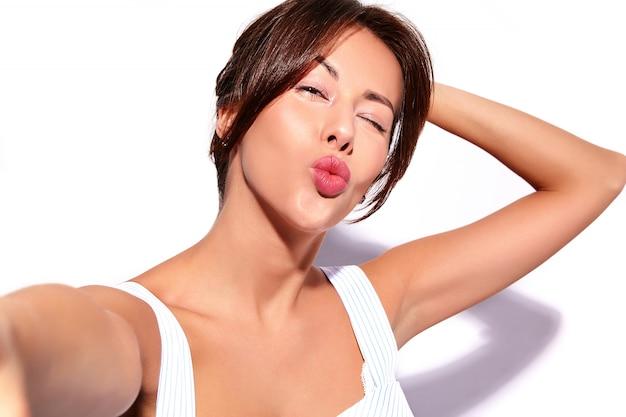 Portret piękny śliczny brunetki kobiety model w przypadkowej lato sukni bez makeup robi selfie fotografii na telefonie odizolowywającym na bielu. pocałunek w powietrzu