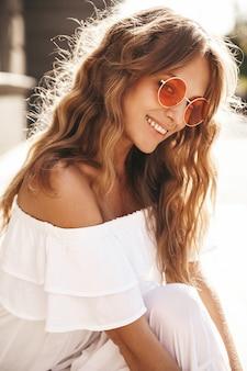 Portret piękny śliczny uśmiechnięty blond nastolatka model bez makeup w lato modnisia bielu sukni ubraniach siedzi na ulicznym tle