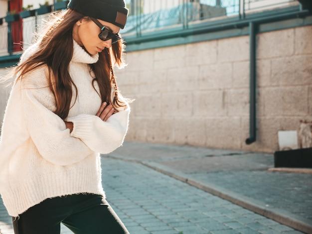 Portret piękny uśmiechający się model. kobieta ubrana w ciepły, hipsterski biały sweter i czapkę. modna kobieta pozuje na ulicy