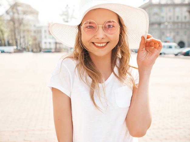 Portret piękny uśmiechnięty blondynu model ubierał w lato modnisiu odziewa. modna dziewczyna pozuje na ulicy w okrągłe okulary przeciwsłoneczne. śmieszna i pozytywna kobieta ma zabawę w kapeluszu