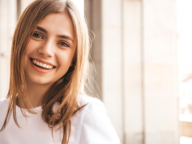 Portret piękny uśmiechnięty blondynu model ubierał w lato modnisiu odziewa.