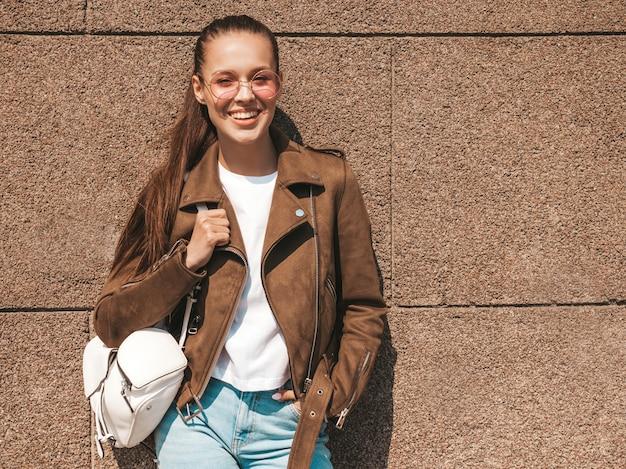 Portret piękny uśmiechnięty brunetka model ubierał w lato modnisia kurtce i cajgach odziewa