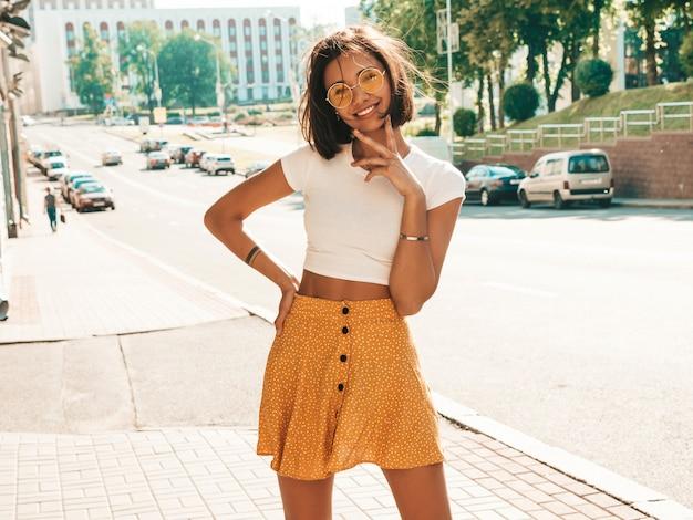 Portret piękny uśmiechnięty brunetka model ubierał w lato modnisiu odziewa. modna dziewczyna pozuje w tle ulicy. śmieszna i pozytywna kobieta ma zabawę