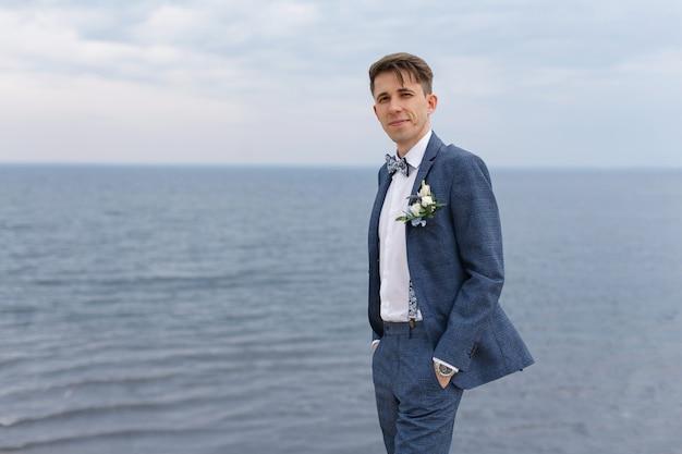 Portret piękny uśmiechnięty młody człowiek w białej koszula i szarości nadaje się outdoors przy tłem nieba i morza