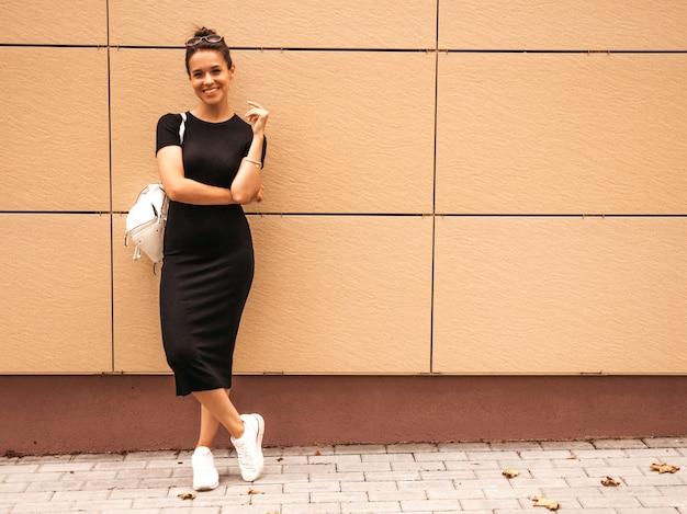 Portret piękny uśmiechnięty model ubierający w lecie odziewa. modna dziewczyna pozuje na ulicy. śmieszna i pozytywna kobieta ma zabawę