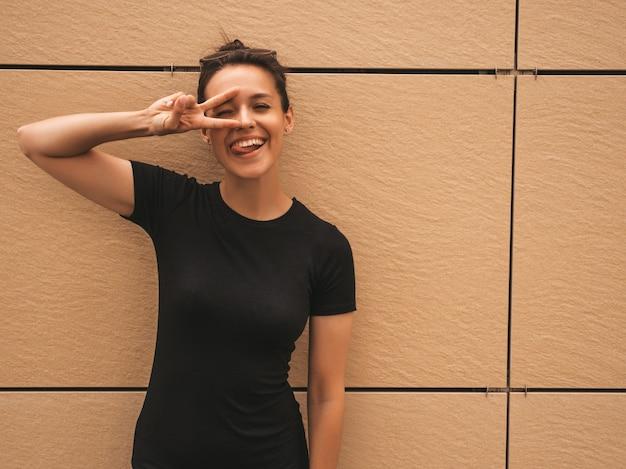 Portret piękny uśmiechnięty model ubierający w lecie odziewa. modna dziewczyna pozuje na ulicy. zabawna i pozytywna kobieta zabawy, pokazuje znak pokoju i język