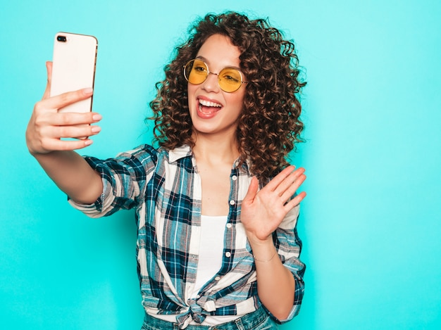 Portret piękny uśmiechnięty model z fryzurą afro loki ubrani w letnie ubrania hipster. modna kobieta śmieszne i pozytywne sprawia, że selfie