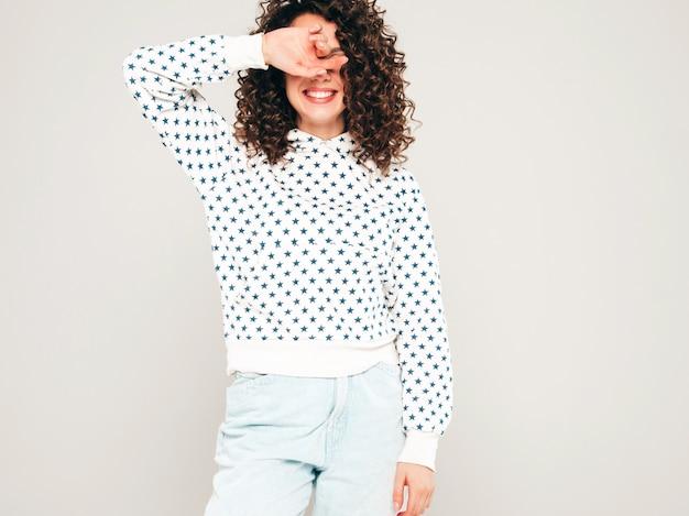 Portret piękny uśmiechnięty model z fryzurą afro loki ubrany w letnie ubrania hipster. seksowna beztroska dziewczyna pozuje na szarym tle. modna śmieszna i pozytywna kobieta w białej bluzie z kapturem