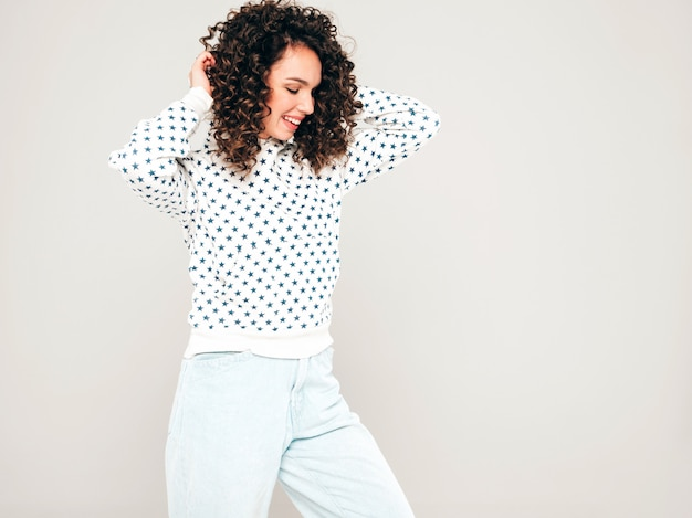 Portret piękny uśmiechnięty model z fryzurą afro loki ubrany w letnie ubrania hipster. seksowna beztroska dziewczyna pozuje w studio na szarym tle. modna kobieta śmieszne i pozytywne
