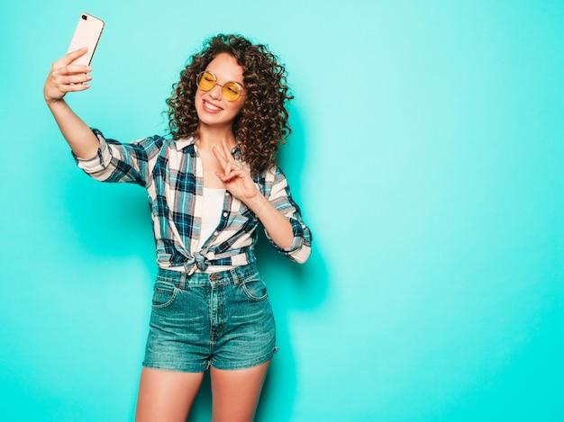 Portret piękny uśmiechnięty model z fryzurą afro loki ubrany w letnie ubrania hipster. seksowna beztroska dziewczyna pozuje w studio na szarym tle. modna śmieszna kobieta bierze selfie zdjęcie