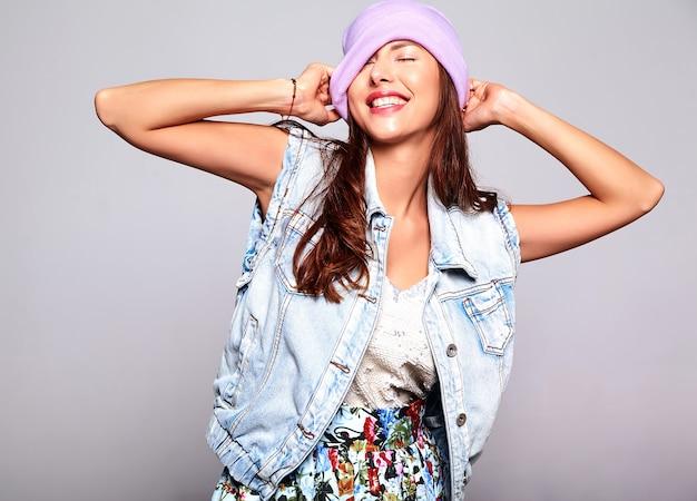 Portret piękny uśmiechnięty śliczny brunetki kobiety model w przypadkowych letnich cajgach odziewa bez makeup w purpurowej czapka odizolowywającej na szarość