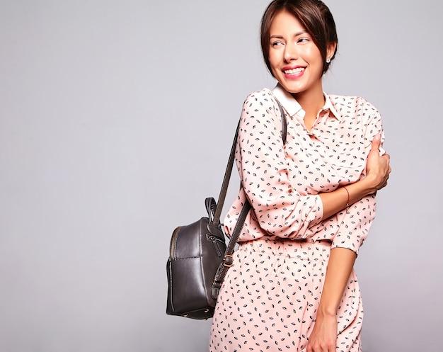 Portret piękny uśmiechnięty śliczny brunetki kobiety model w przypadkowym lecie odziewa bez makeup odizolowywającego na popielatej ścianie z handback