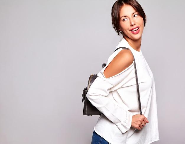 Portret piękny uśmiechnięty śliczny brunetki kobiety model w przypadkowym lecie odziewa bez makeup odizolowywającego na popielatym