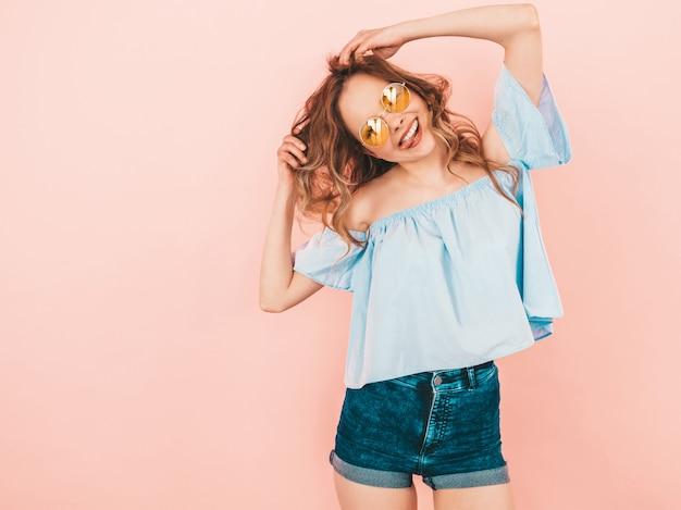 Portret piękny uśmiechnięty śliczny model w round okularach przeciwsłonecznych. dziewczyna w kolorowe ubrania letnie. pozowanie modelu. zabawa z jej włosami