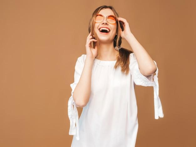 Portret piękny uśmiechnięty śliczny model z różowymi wargami. dziewczyna w białej letniej sukience. model stwarzające w okularach przeciwsłonecznych