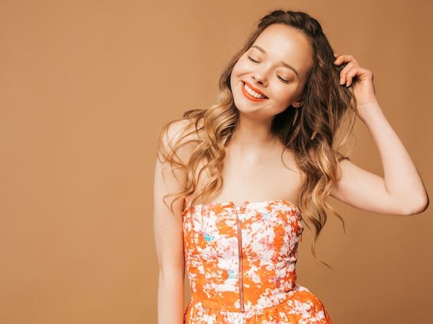 Portret piękny uśmiechnięty śliczny model z różowymi wargami. dziewczyna w letniej kolorowej sukience. pozowanie modelu. zabawa z jej włosami