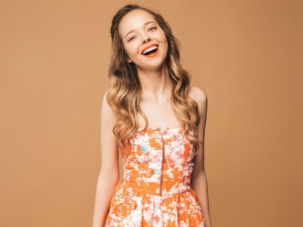 Portret piękny uśmiechnięty śliczny model z różowymi wargami. dziewczyna w letniej kolorowej sukience. pozowanie modelu