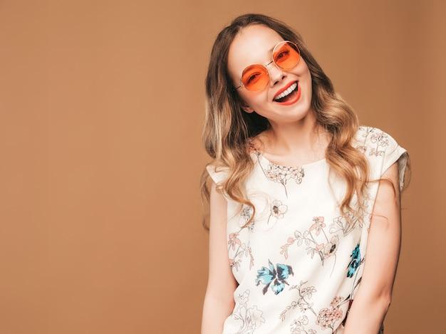Portret piękny uśmiechnięty śliczny model z różowymi wargami. dziewczyna w letniej sukience kolorowe i okulary przeciwsłoneczne. pozowanie modelu