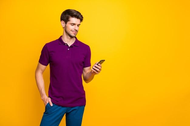 Portret piękny wesoły facet ubrany w fioletową koszulkę za pomocą gadżetu urządzenia, wpisując wiadomość sms na czacie na białym tle