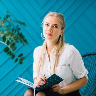 Portret piękny żeński psycholog z diary i pióra obsiadaniem na krześle przed błękitem patrzeje kamerę