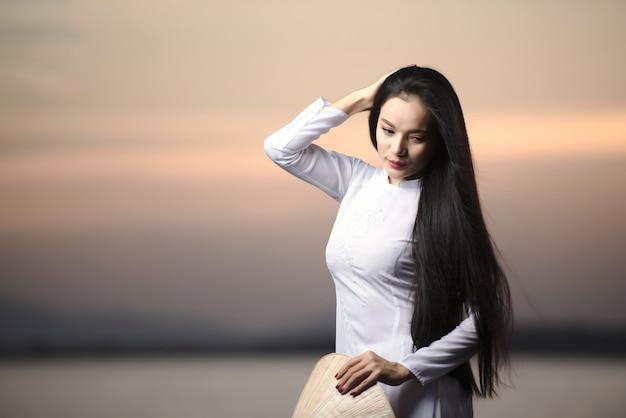 Portret pięknych azjatyckich dziewcząt z tradycyjnym strojem ao dai wietnam na krajobrazy zachodu słońca.