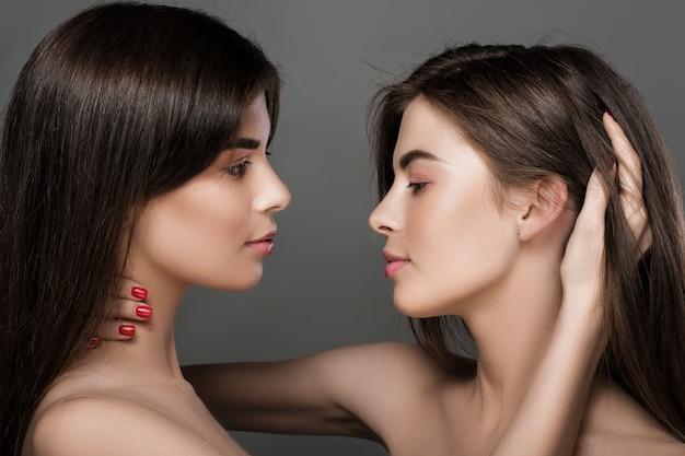 Portret pięknych bliźniaczek o doskonałej skórze i naturalnym makijażu oraz długich włosach. moda