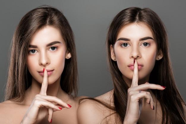 Portret pięknych bliźniaczek z idealną skórą gestykulującą ciszę
