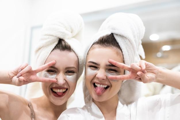 Portret pięknych europejskich dziewcząt wystających języków i pokazujących gesty zwycięstwa. młode kobiety z przepaską pod oczami na twarzy i owiniętymi ręcznikami kąpielowymi na głowach. koncepcja imprezy dla dziewczyn