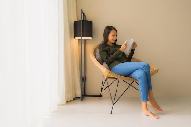 Portret pięknych młodych azjatykcich kobiet czytelnicza książka i obsiadanie na kanapy krześle