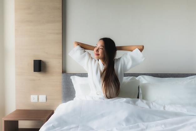 Portret pięknych młodych azjatykcich kobiet szczęśliwy uśmiech relaksuje na łóżku