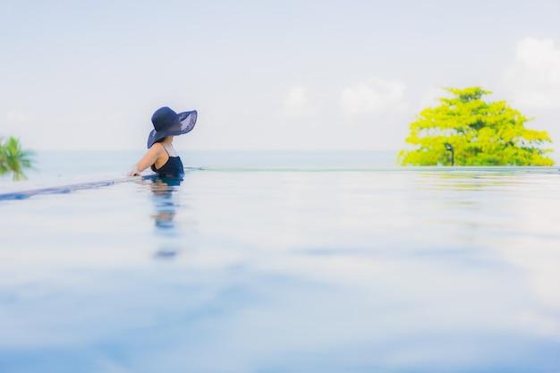 Portret pięknych młodych azjatykcich kobiet szczęśliwy uśmiech relaksuje plenerowego pływackiego basenu w hotelu