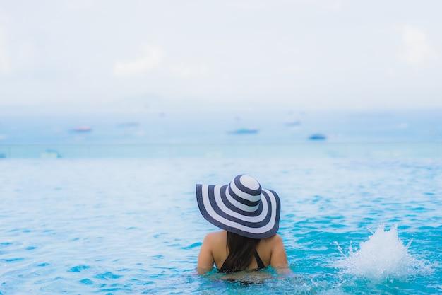 Portret pięknych młodych azjatykcich kobiet szczęśliwy uśmiech relaksuje plenerowego pływackiego basenu w kurorcie