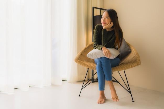 Portret pięknych młodych azjatykcich kobiet szczęśliwy uśmiech relaksuje siedzieć na kanapy krześle