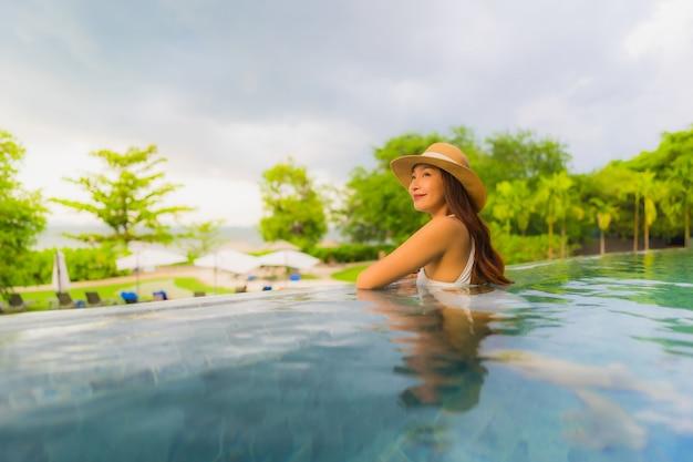 Portret pięknych młodych azjatykcich kobiet szczęśliwy uśmiech relaksuje wokoło plenerowego pływackiego basenu w hotelu